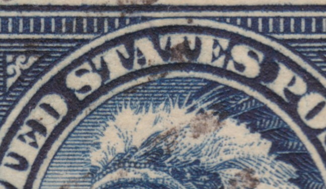 "Detail of 14¢ American Indian stamp showing traces of possible double transfer in ""UNITED STATES"" lettering"